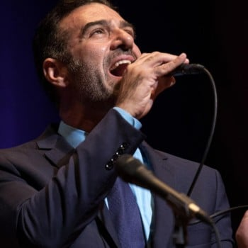 Vocalist Paul Marinaro holding a microphone singing
